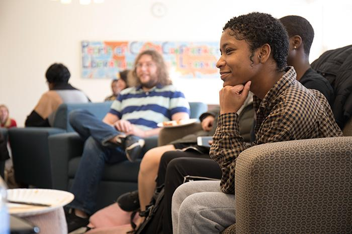 Students seated on comfy furniture have a discussion.