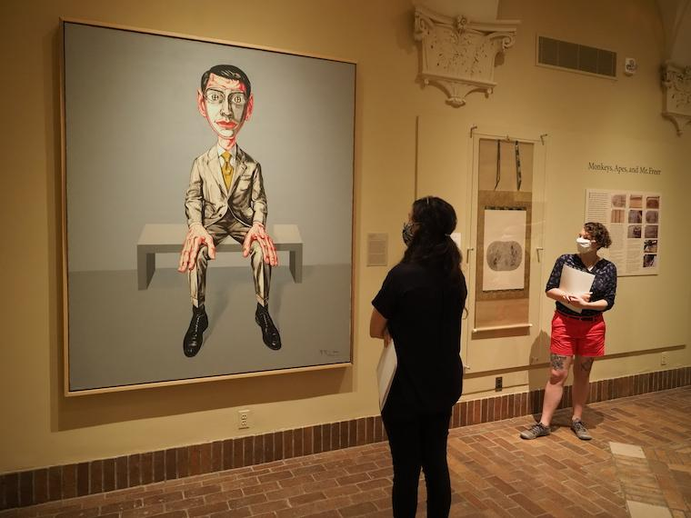 students look at large painting of man sittig in chair