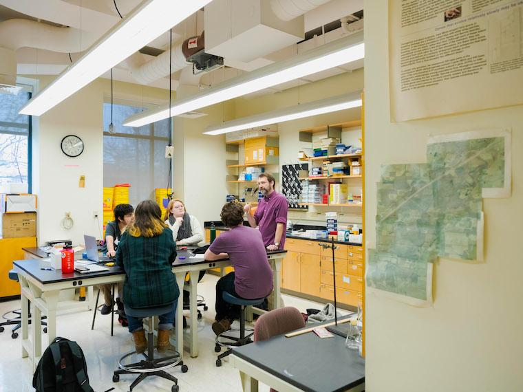 four students sitting at lab table with professor standing in front.
