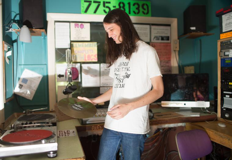 Student smiling and looking at a record in the WOBC DJ booth
