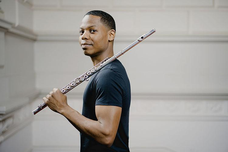 Black man in black t-shirt looking at the camera and holding flute over his shoulder.