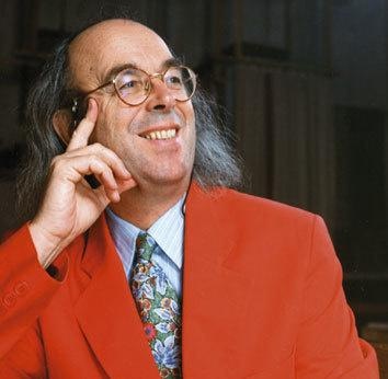 guy bovet wearing a red jacket, glasses and smiling as he looks to the side