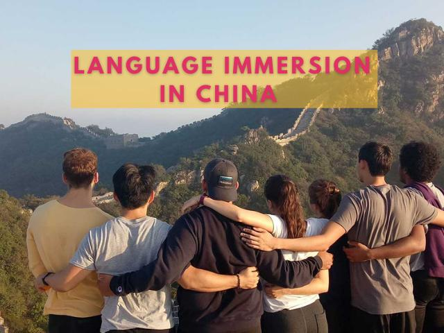 Six students look out across the Great Wall of China.