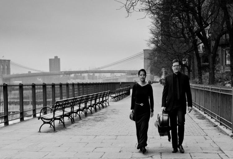 Caroline Chin and Brian Snow walk side by side carrying their instrument cases along a riverfront sidewalk with a bridge in the background