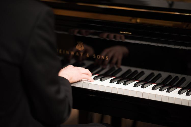 Image of person pressing keys on a Steinway & Sons piano