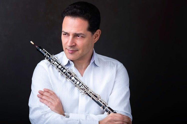 Eugene Izotov looking to his right - waering a white shirt and holding oboe across his chest
