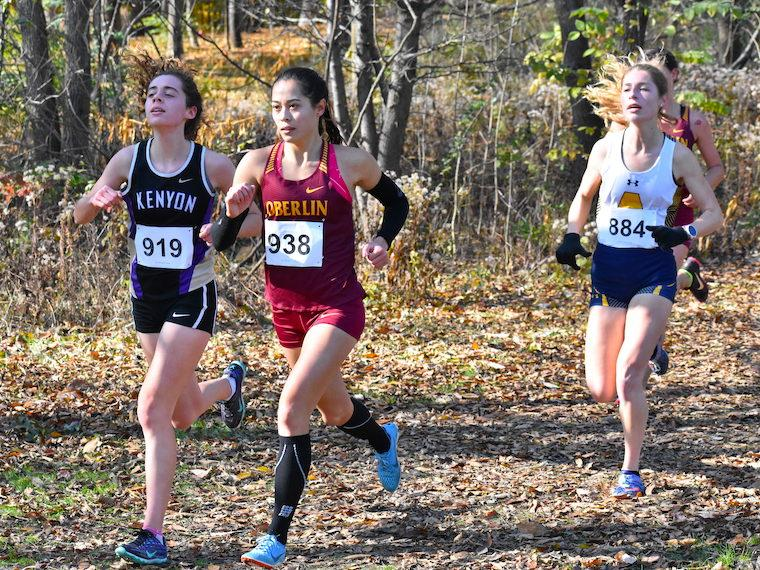 three women running cross country along wooded area.