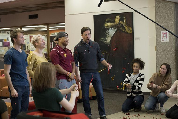 A video crew tosses confetti while alumnus Ed Helms is on camera with students.