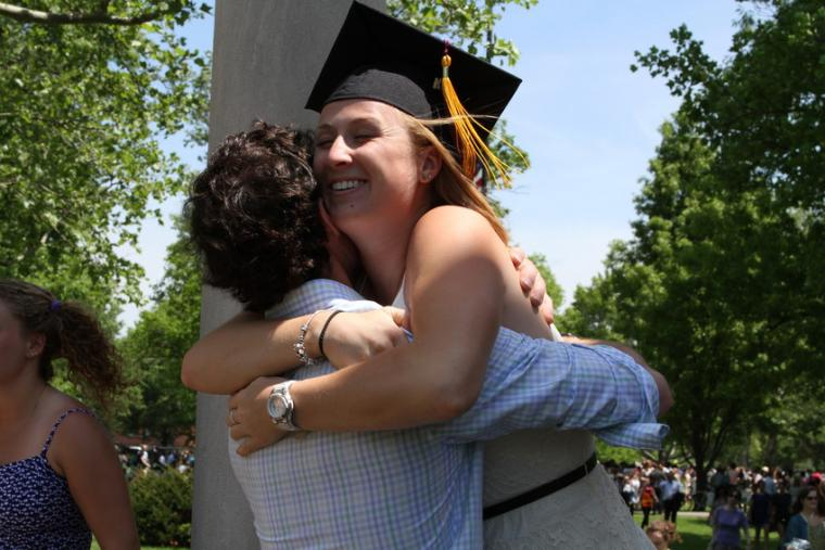 A woman wearing a commencement cap embraces another person outdoors