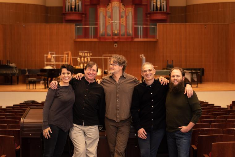 Five people standing in front of the stage in Warner Concert Hall; Elizabeth Ogonek, Stephen Hartke, Xak Bjerken, Timothy Weiss, and Jesse Jones.