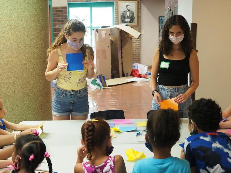 Two college students teach a group of young children the art of origami