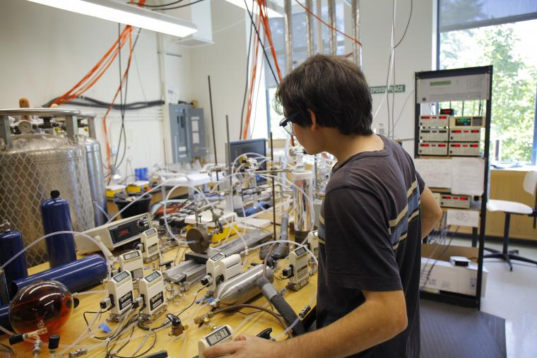 William Burke makes adjustments to instruments in Matthew Elrod's lab.