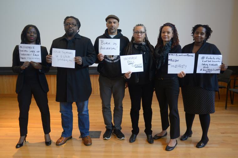 6 professors holding handwritten signs. Complete text follows.