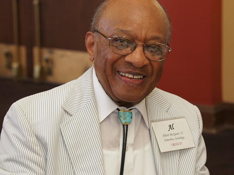 black man with glasses, dressed in beige-striped suit and smiling.