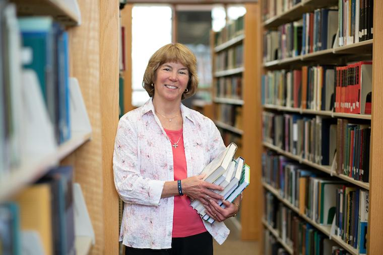 Picture of woman holding a stack of books in library