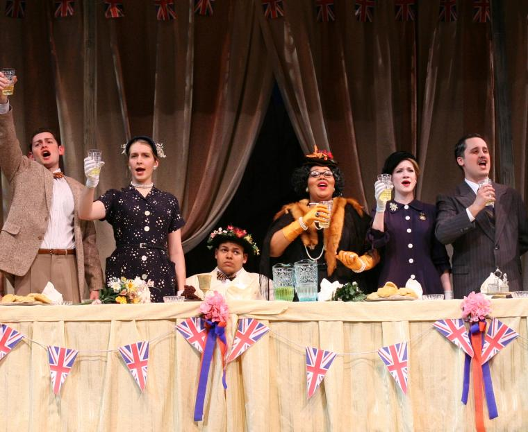 In a scene from the production, performers stand at a long table with glasses raised.