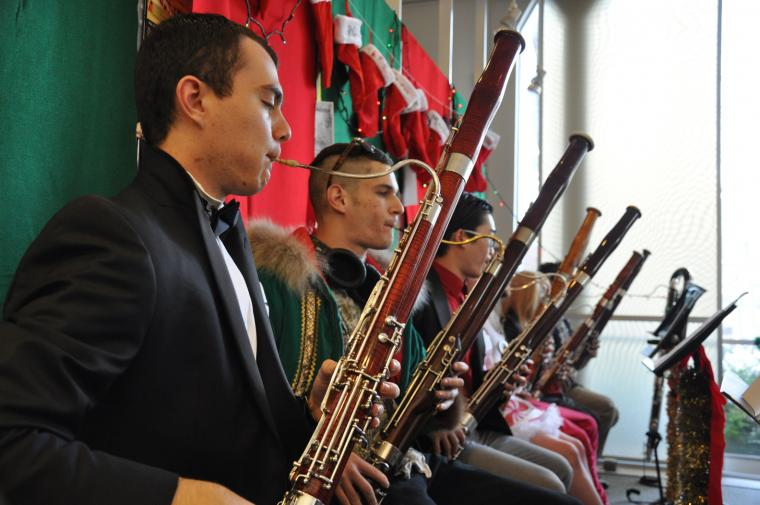 Bassoonists seated under a row of Christmas stockings