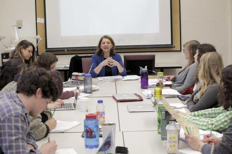 Ana Cara leads a discussion with students around a table.
