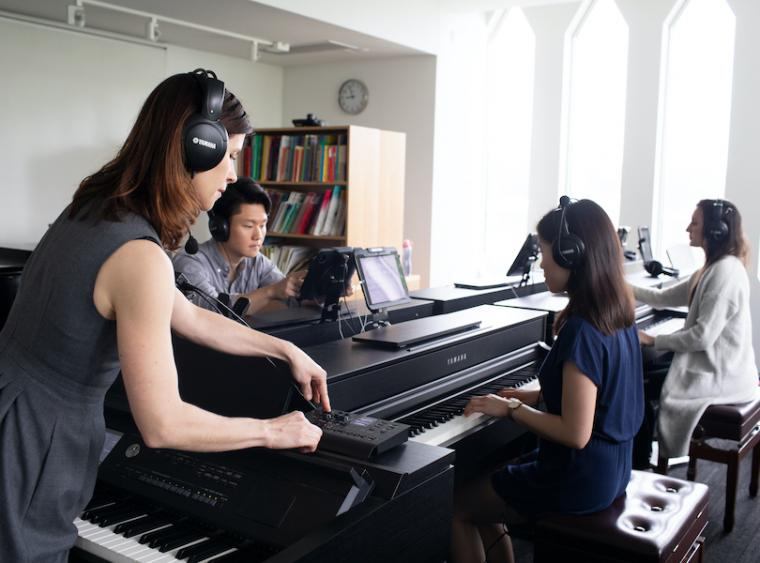 teacher working with students at keyboards in a piano pedagogy lab.