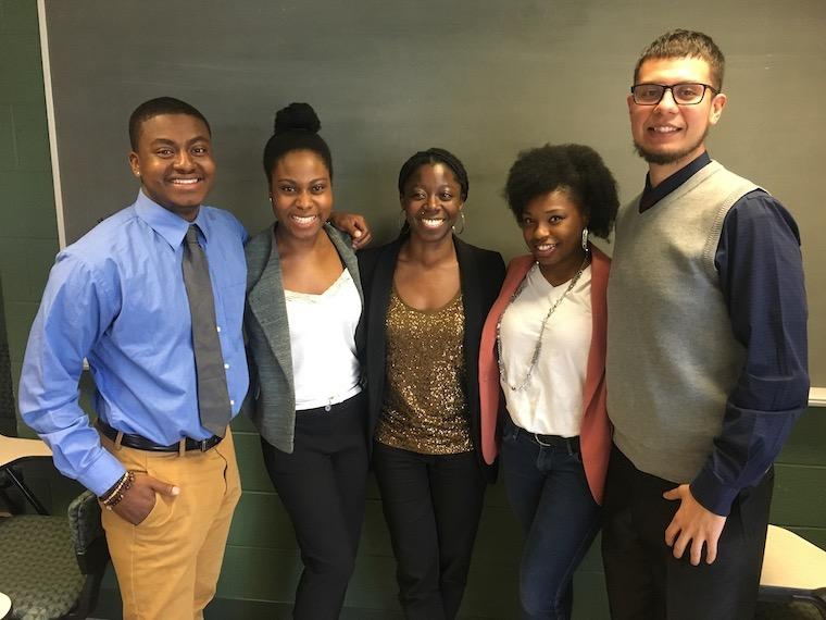 Andre Cardine, Thoebeka Mnisi, Afia Ofori-Mensa, Niya Smith, and Brian Cabral stand next to each other with their arms around each other in the King building