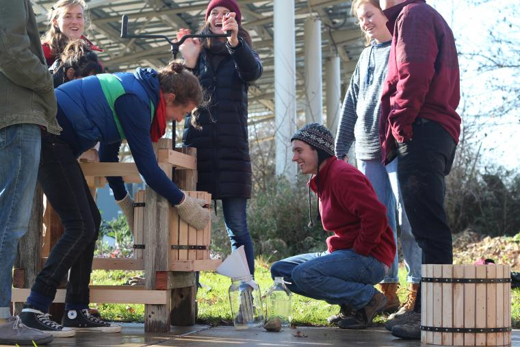 A group of students using a hand-cranked cider press.