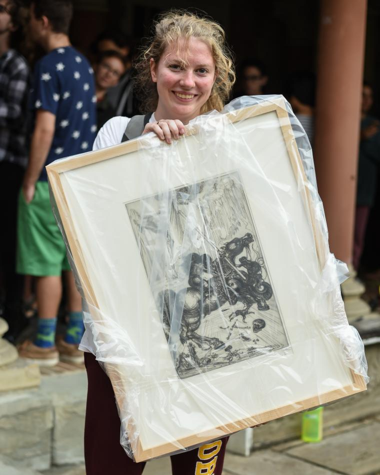 Student holds a framed drawing, which is wrapped in plastic.