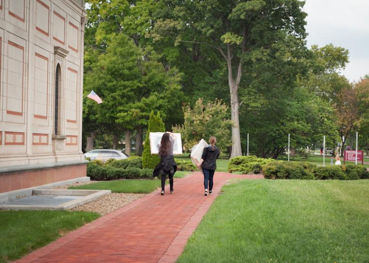 Two students walk away from the museum, each carrying a framed artwork.