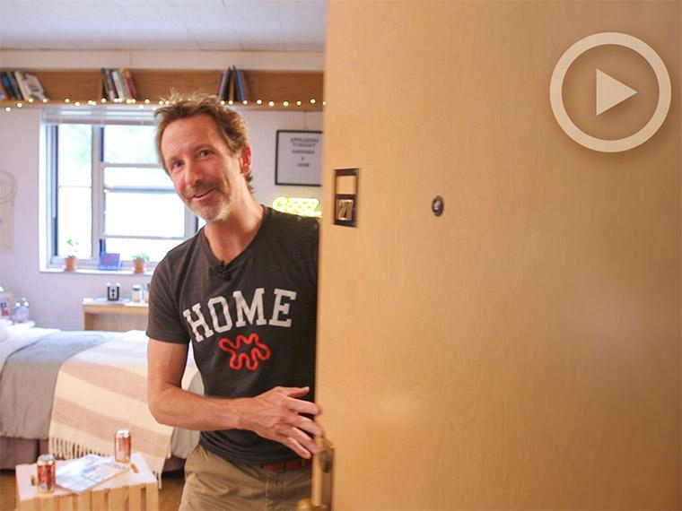 man standing in dorm room doorway