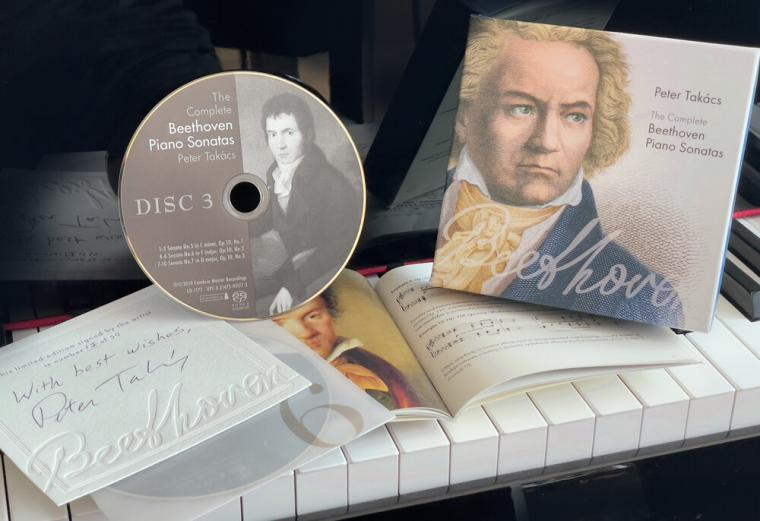 CD and package placed on a piano keyboard.