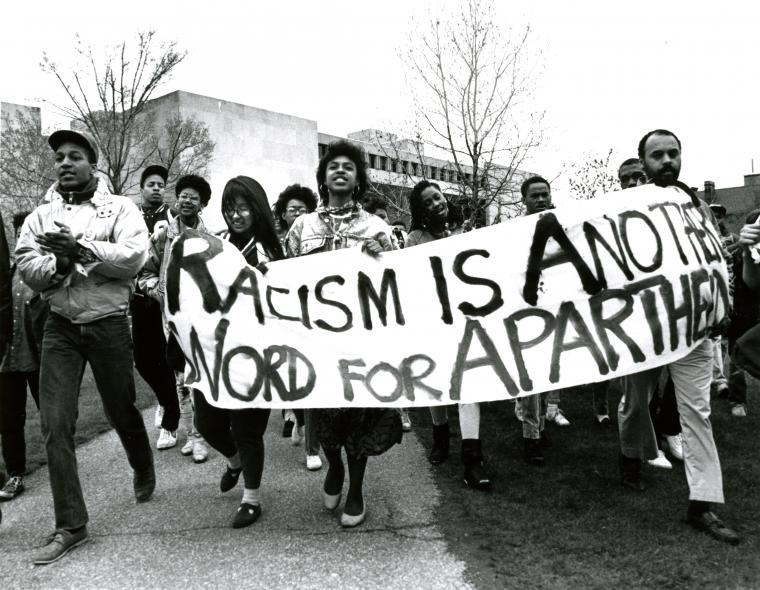 Protesters in front of the main library carry a banner that says Racism is Another Word for Apartheid.