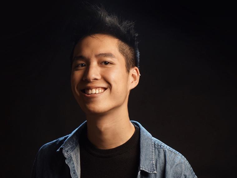Asian man smiling and wearing a black shirt and jean shirt.