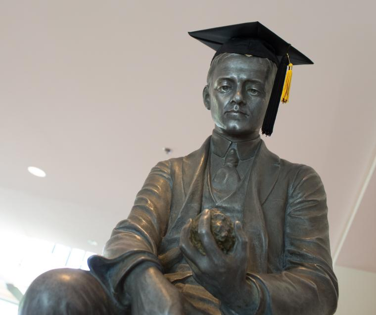 Statue of a man, with a graduation cap placed on its head.
