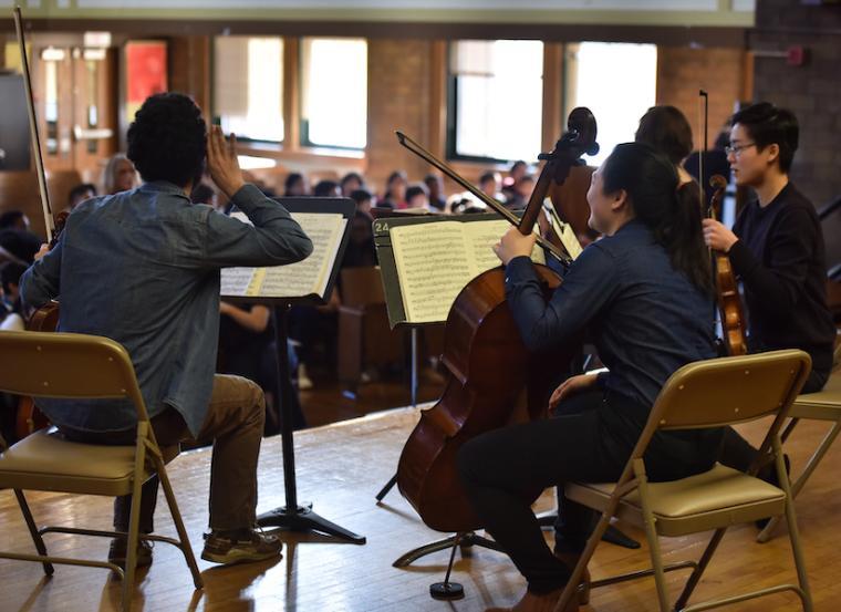 string ensemble musicians performing for children.