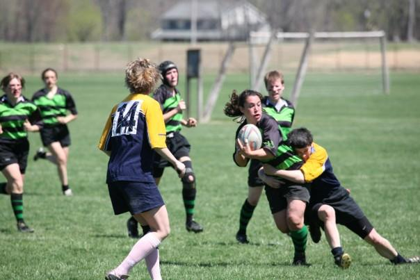 A rugby player with the ball is tackled while other players run toward them.