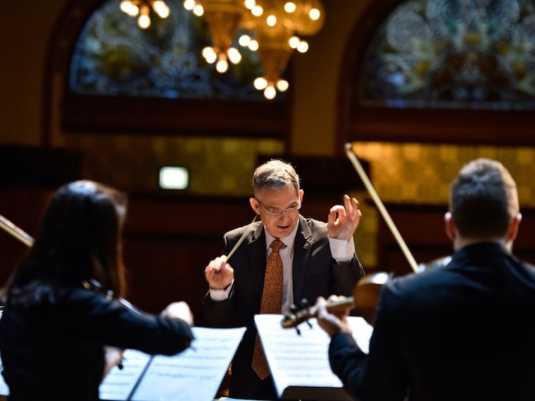 Conductor leading musicians in performance.