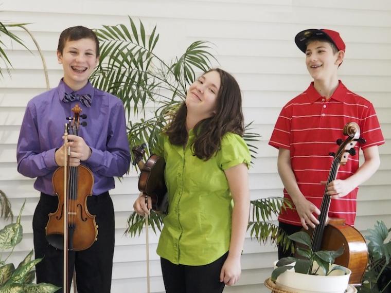 three children with string instruments.