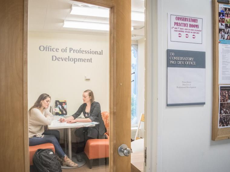 career advisor working with a student in an office.