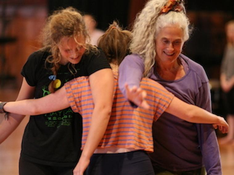 Three contact dancers standing together locked arm-in-arm