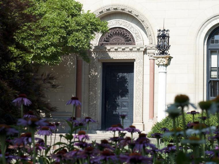 Cox Administration Building entry door framed by tree and flowers