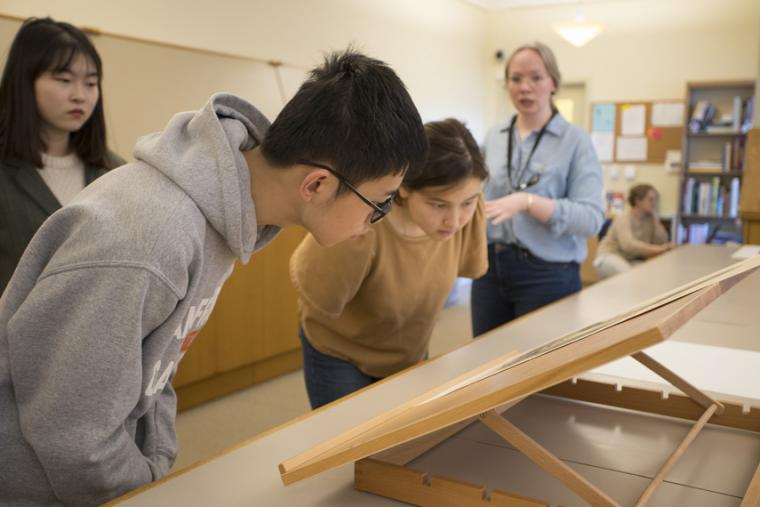 two students bent over looking at a lithograph.