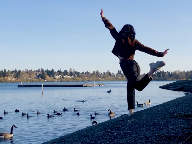 student in brown jacket and dark pants dances in front of a pond with ducks.