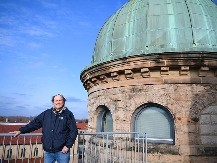 man standing next to a observatory dome