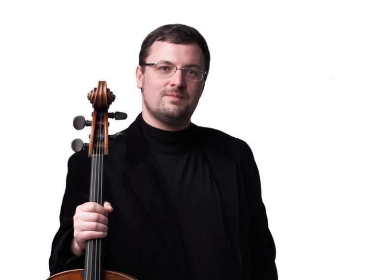 cello faculty member Dmitri Kouzov holding his cello.