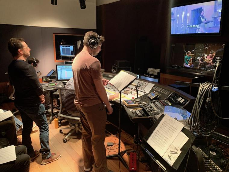 an Oberlin student works in the recording studio with audio production staff and a guest composer.