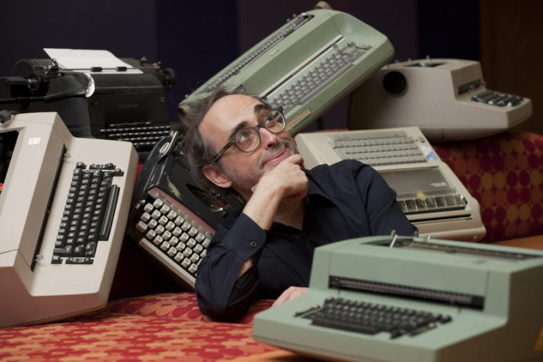 Gary Shteyngart makes a silly, introspective pose amidst typewriters