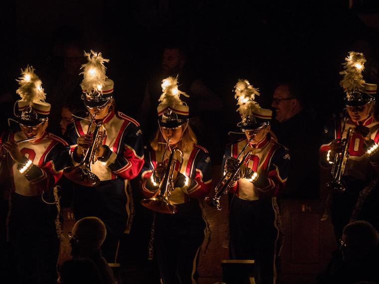 A marching band performs indoors, in the dark, with lights shining from their hats and uniforms.