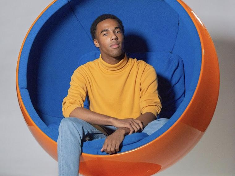 """young black man sitting in a  circular """"womb"""" chair."""