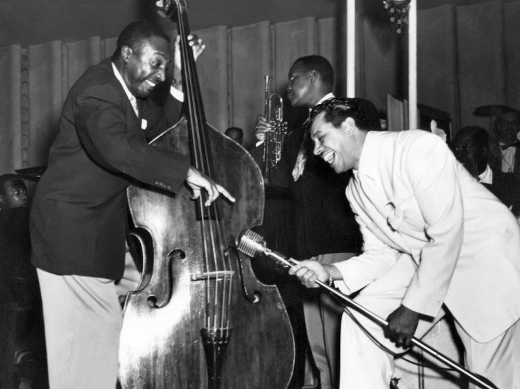 man playing upright bass next to man holding microphone stand