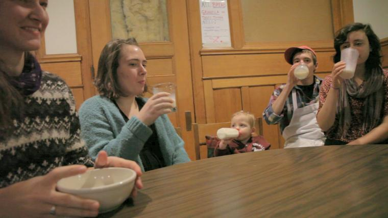 A baby drinking from a bottle fits right in with Tank co-op members drinking milk.