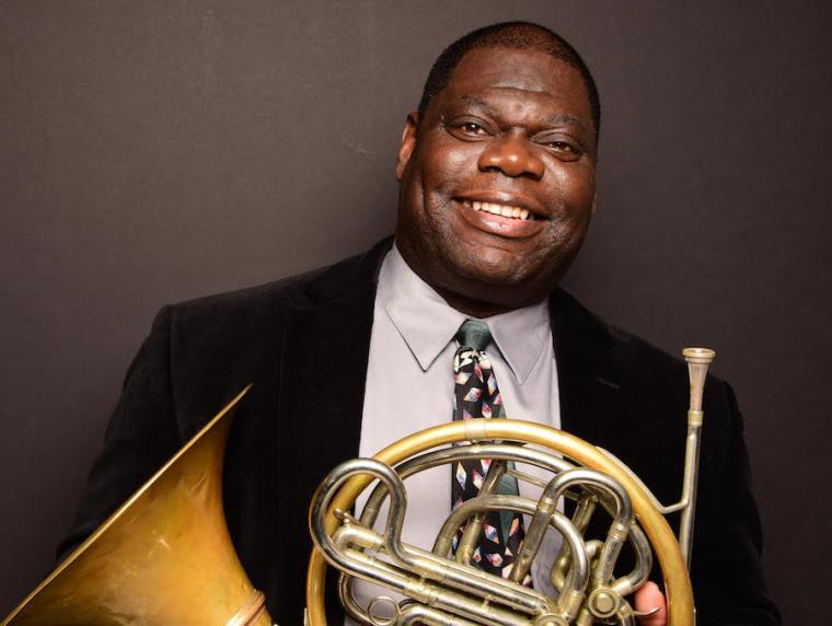 horn professor Jeff Scott holding his french horn.